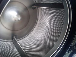 Clothes dryer or tumble dryer automatically. Inside the perforated stainless steel drum, black and white metal background. Focus close and choose the subject.
