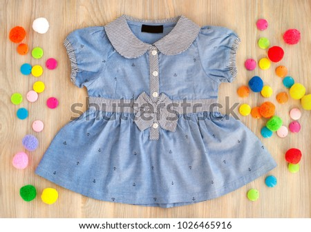 Clothes for children from jeans. Blue dress for the girl on a wooden background. View from above. Summer clothes for children. Lush dress with a bow. Clothing for kinder.