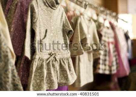 Clothes for little girls in a fashion shop. Shallow focus.