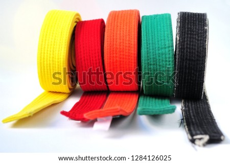 Clothes for martial arts - karate, aikido, judo. Colored belts on a white background.