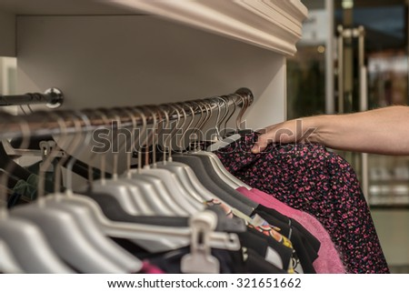 Clothes hang on a shelf in a clothes store. Close up, selective focus.