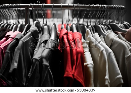 Clothes hangers with red t-shirts in store ready to choose to buy. Fashion shopping concept