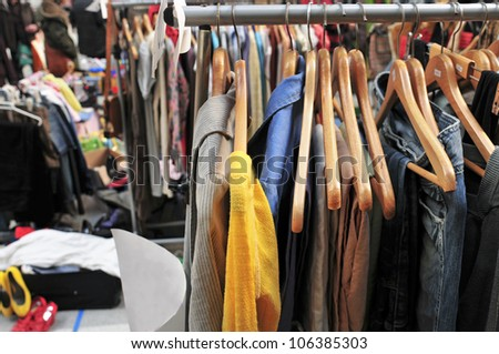 clothes hanging on a rack in a flea market
