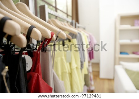Clothes hanging on wooden hangers in a fashion store.