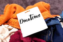 Clothes heap. there is a large pile of sketched clothes, notebook with donations, coat drive, donation concept