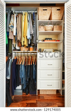 Clothes hung neatly in organized closet at home #129174005