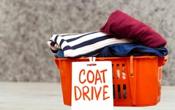clothes in orange basket or box with coat drive, donation concept