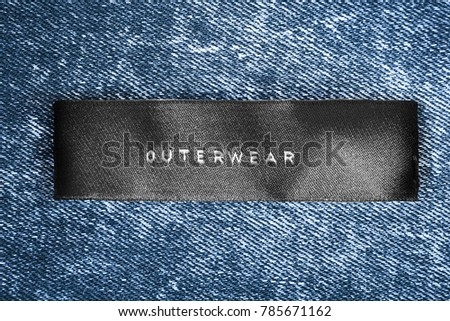 Clothes label lettered outerwear on blue denim background - Shutterstock ID 785671162