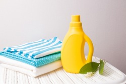 clothes made of colored fabric, lily of the valley flower and fabric softener in a yellow plastic bottle without a label on a captive basket, fabric softener with lily of the valley aroma