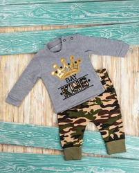 Clothes made of sweaters with a pattern of crown and camouflage paintings for the kid lie on a hundred