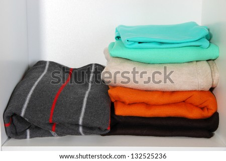Clothes neatly folded on shelves #132525236