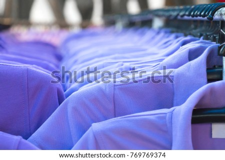 Clothes on clothes rail in clothing store. Interior of fashions outlet shop.  #769769374