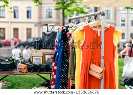 Clothes on the rail on the summer outdoor vintage fashion designer market. Garage sale, reuse the clothes, second hand and eco consumering