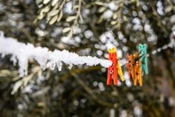 Clothes pegs covered by snow on the rope outdoor.