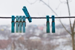 Clothes pegs on the wire with ice on them - Winter time concept.