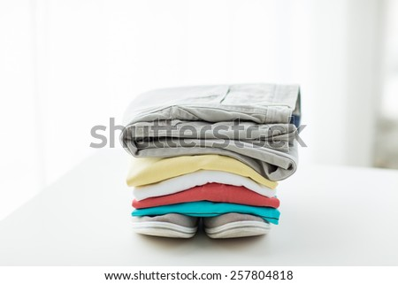 clothes, personal staff and objects concept - close up of folded shirts, pants and shoes on table at home