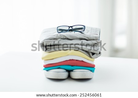 clothes, personal staff and objects concept - close up of folded shirts, pants, glasses and shoes on table at home