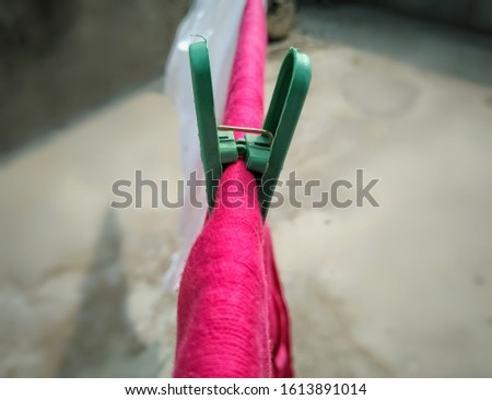 clothes pin, clothes line rope, drying pink cloth outside, laundry clip