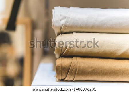 clothes ,sale, shopping, fashion, style concept - Stack of chino pants ,Cream , Brown and khaki color, in the shopping mall Foto stock ©