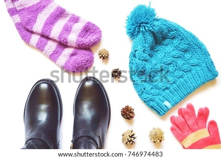 Clothes stuff. Purple socks, leather boots, pine cones, blue woolen knitted hat and pink gloves. Fall fashion. Autumn and winter women's clothes. Flat lay stock photography for fashion blog