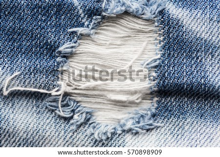 clothes, wear and fashion concept - close up of hole on shabby denim or jeans