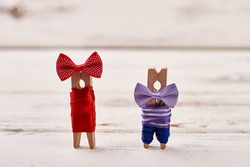 Clothespin couple on white backdrop. Dressed up clothes pegs. Art and household items.