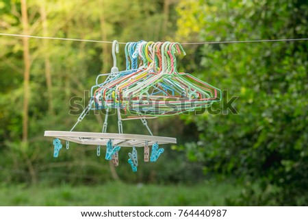 Clothespin hang in outdoor with nature green background.