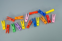 Clothespins are in a chaotic pattern on a gray background. Business concept. Cover. Web banner.