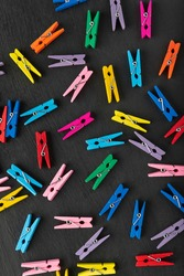 Clothespins of different colors in chaotic manner on black background. Top view. Vertical frame