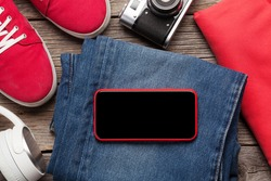 Clothing and accessories. Sneakers, camera and smartphone with blank screen over jeans. Urban outfit for everyday or travel vacation on wooden background with copy space on phone screen