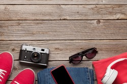 Clothing and accessories. Sneakers, jeans, headphones and smartphone. Urban outfit for everyday or travel vacation on wooden background with copy space. Top view flat lay