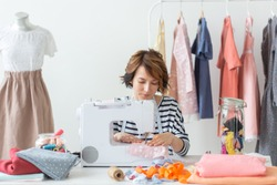 clothing designer, seamstress, people concept - woman seamstress working in her studio