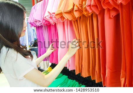 Clothing, Fashion, Style and People Concept. Young Asian Woman Buying Clothes in a Shopping Mall Store. Female Choosing or Searching Colorful Shirt Sale on Hanger in Women is Cloths Shop Background.