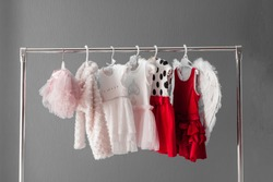 Clothing for a little girl on a clothes rack in a wardrobe
