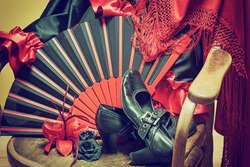 Clothing for Flamenco dance. Black shoes, fan, red scarf with tassels and paper roses are lying on a vintage wooden chair. Edited as a vintage photo with dark edges.
