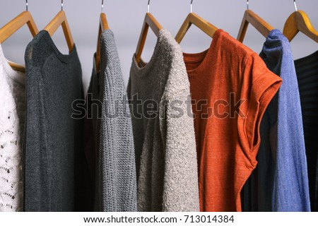 Clothing hanging on a clothing rack in a shop or home closet.
