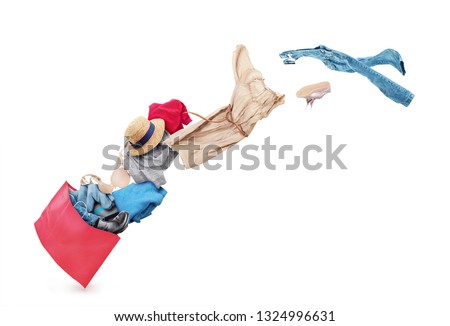 Clothing is flying from the paper bag on a white background #1324996631