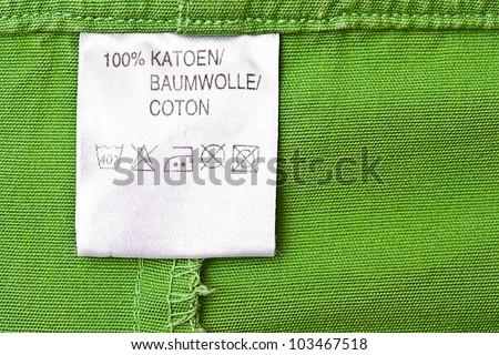 Clothing label washing instruction tag on green t-shirt