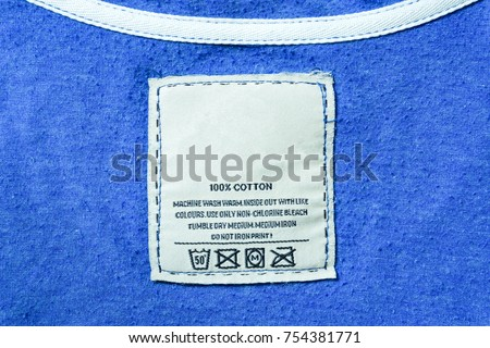 Clothing label with laundry instructions, close-up of person reading the clothing label showing washing Instructions,clothes, housekeeping concept.