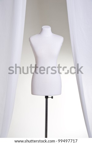 Clothing mannequin white on a light background near the curtains