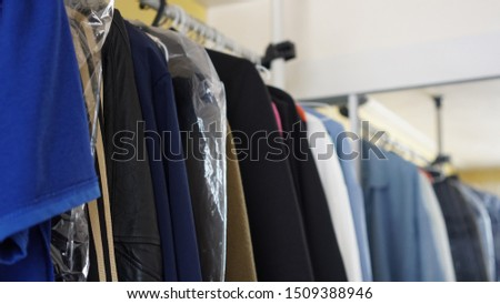 clothing on hangers at the living room. winter Cloth or summer cloth