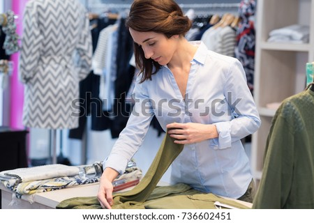 clothing shop worker folding cloth