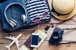 Clothing traveler's Passport, wallet, glasses, smart phone devices, on a wooden floor in the luggage ready to travel.