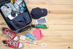 Clothing traveler's Passport, wallet, glasses, watches, smart phone devices, on a wooden floor in the luggage ready to travel.
