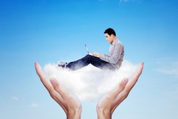 Cloud computing concept. Close up of young man working with a laptop while sitting on a hand with white cloud