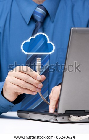 Cloud computing concept. Man send data from laptop to cloud represented by icon via ethernet cable. Selective focused on cable.