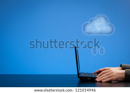 Cloud computing concept - man working with laptop and cloud represented by icon. Blank negative space for your texts and design on left.