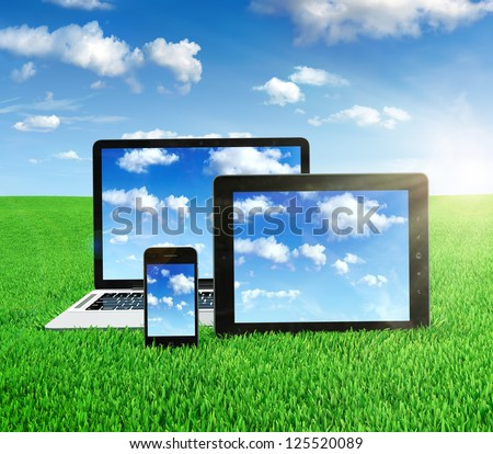 Cloud computing concept on different electronic devices. Tablet computer, laptop and smartphone in the middle of the field with sky image on screen.