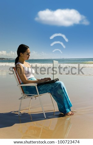 Cloud computing: woman with laptop working at the beach
