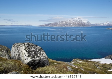 Cloud covered Sermitsiaq mountain seen from Nuuk with a large boulder in the foreground